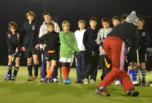 Coach demonstrates a technique to the boys at Oxford Hockey Club's academy training